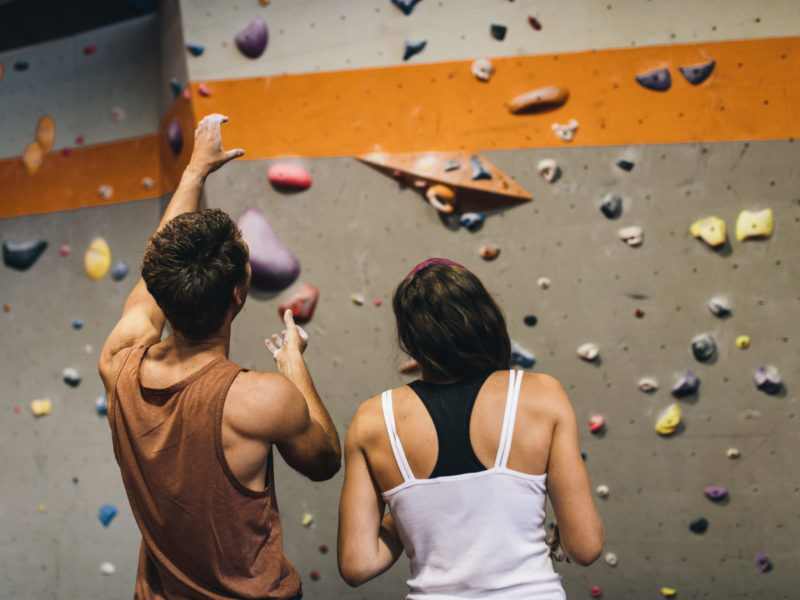 photo of man and woman standing in front of climbing wall